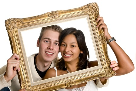 origin: Happy couple of different ethnic origin, showing their love in a frame Stock Photo