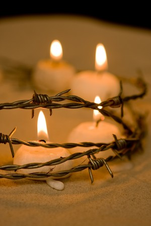 Burning candles behind barbed wire, symbol of hope photo