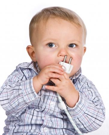 descarga electrica: Curioso beb� jugando un juego peligroso con un enchufe el�ctrico Foto de archivo