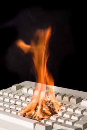 Old computer keyboard on fire due to fast typing? Stock Photo