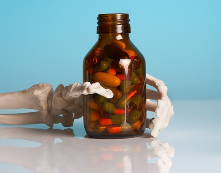 suicidal: Skeleton hand holding a brown bottle full of pills