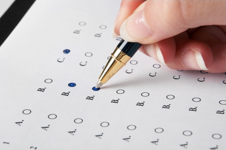 filling in: Hand filling in an evaluation form with a pen