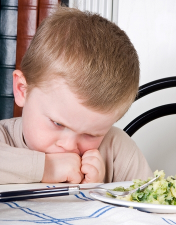 dislike: Four year old boy disliking the food on his plate