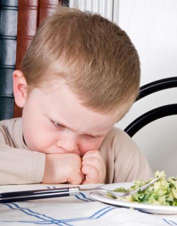 dislike: Vier jaar oude jongen disliking het voedsel op zijn bord Stockfoto