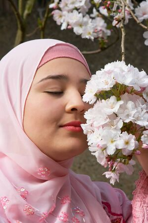 purdah: Young woman with a pink silk veil smelling pink spring blossoms Stock Photo