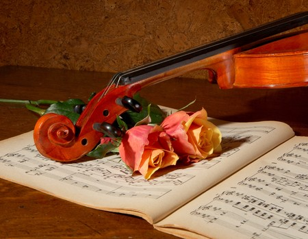 Vintage still life with a violin, music book and soft roses photo