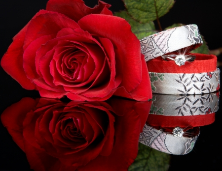Diamond ring in a box, and a red rose, ready for valentines day