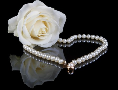 true: White pearl necklace and beautiful white rose on a black background - a valentine gift Stock Photo