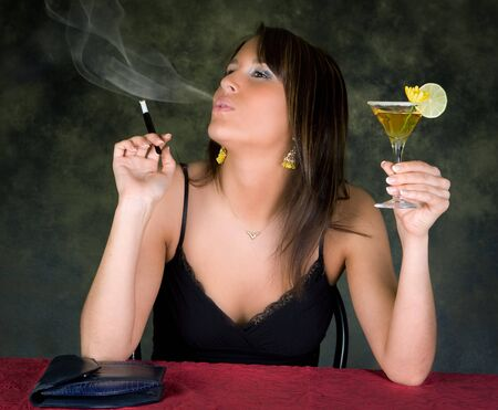 women smoking: Young woman waiting for her partner holding a cocktail Stock Photo