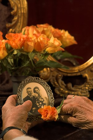 flower photos: Old hands holding a sepia wedding photograph Stock Photo