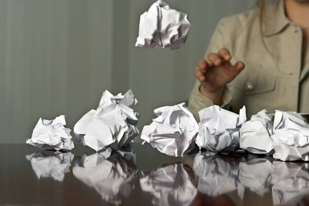 writers block: Woman throwing waste paper balls on the table