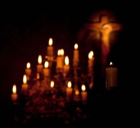 prayer candles: Holy cross and candles lighting in the darkness