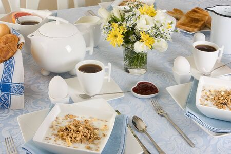 Elegant breakfast table with cereals, eggs, flowers and toast photo