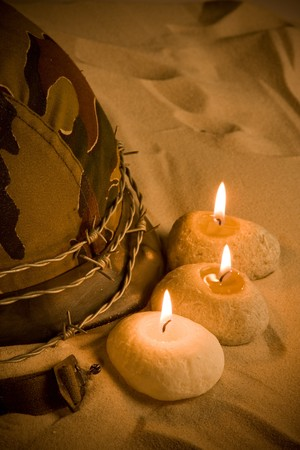 Barbed wire, candles and a helmet lying in the sand photo