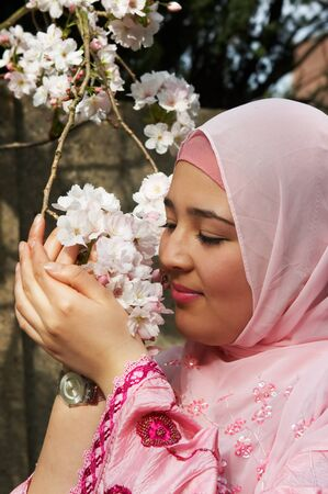 purdah: Young moroccan woman holding pink spring blossoms in her hands