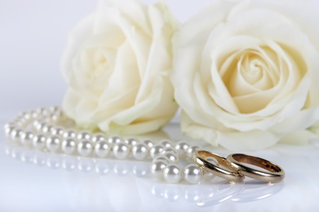 Couple of worn wedding rings and pearls, with two fresh white roses photo