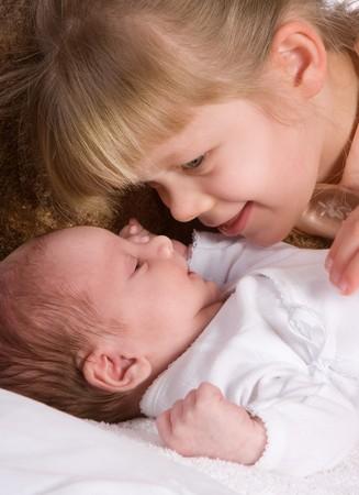 Little girl admiring her newborn little brother photo