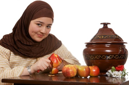 Young islamic woman preparing food and peeling an apple photo