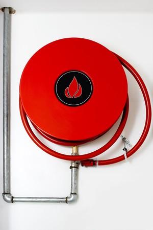 borne fontaine: Rouge Bobine de bornes d'incendie sur un mur en attendant l'action