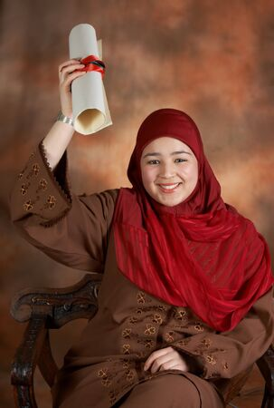 the emancipation: Traditionally veiled Moroccan student waiving with her diploma
