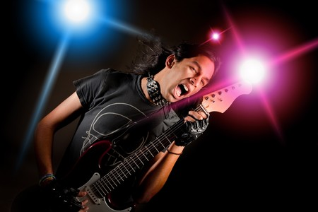 Young handsome rock singer against a dark background with spot lights Stock Photo - 4283310