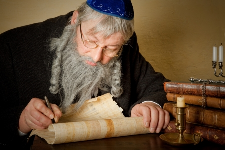 Old jewish man with beard writing on a parchment scroll photo