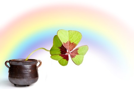Brown pot with four-leaf clover and a rainbow Stock Photo - 4287415