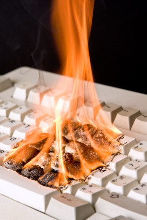 ruined: Closeup of an old computer keyboard on fire Stock Photo