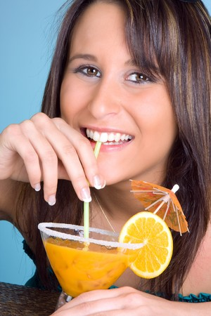 Young woman drinking an orange cocktail with a smile photo