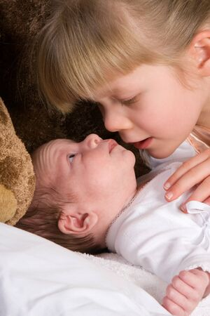 Portrait of a girl with her newborn brother photo