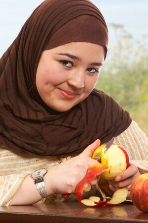 Young islamic woman peeling a red apple photo
