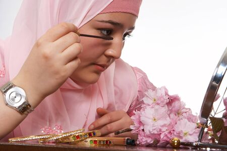 purdah: Young islamic beauty applying mascara to her eye-lashes Stock Photo