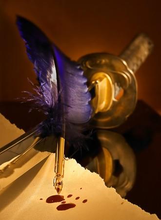 pluma de escribir antigua: La pluma es m�s fuerte que la espada o: Palabras duele m�s de Espadas Foto de archivo