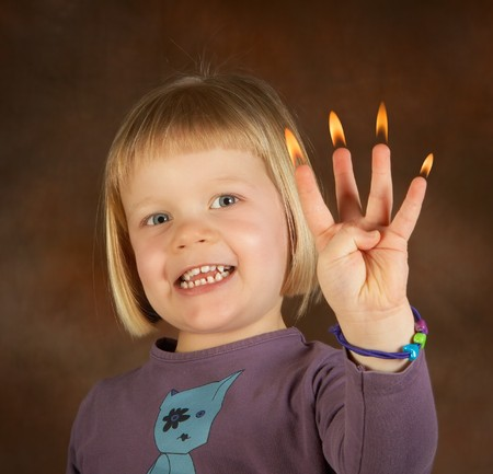 Little girl on her fourth birthday, showing how old she is, with a little flame on every finger photo
