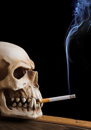 Skull smoking a cigarette, smoke against a black background photo