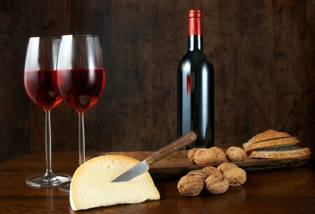 bread and wine: Bread, wine, cheese and nuts on a wooden table Stock Photo