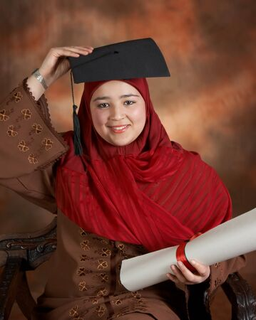 Happy islamic student holding her graduation cap above her traditional veil photo