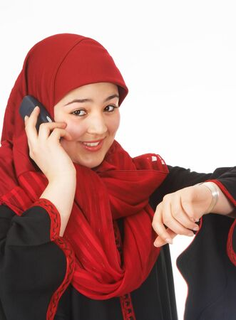 Young islamic woman making a phone call and looking at her watch photo