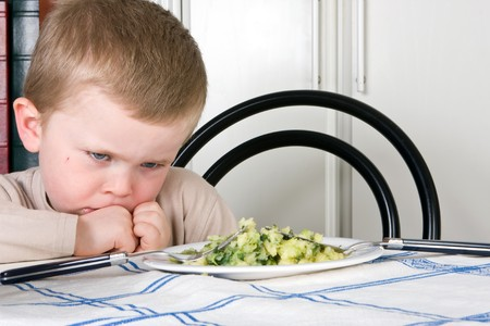 Four year old boy refusing to eat his dinner photo