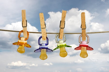 Colored baby pacifiers hanging outside in line photo