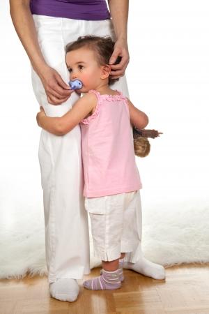 Sad little girl holding her mothers legs Stock Photo