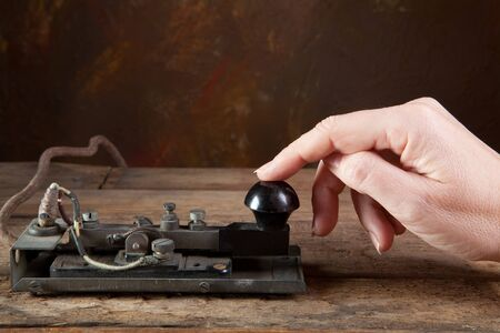 tapping: Hand tapping morse code on an antique telegraph