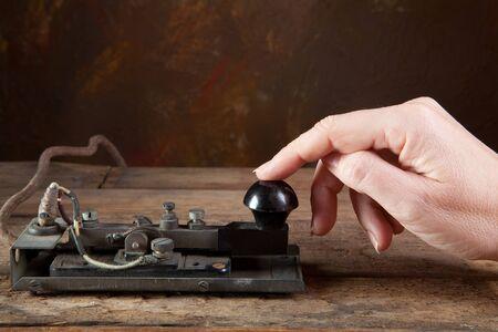 tapping: Mano toccando codice morse su un antico telegrafo