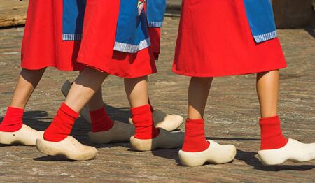 footware: Close-up of wooden shoes, worn by three Dutch girls Stock Photo