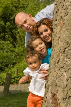 Older father posing with his happy family behind a tree photo