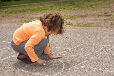 hopscotch: Little girl drawing squares on the street, for hopscotch Stock Photo