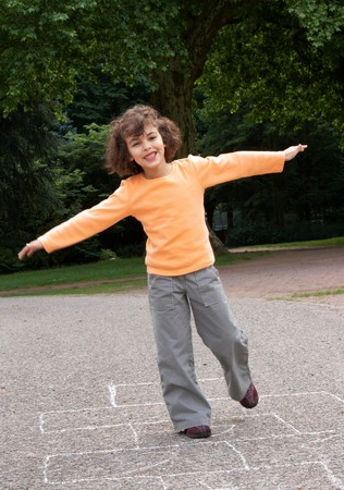 Little girl playing hopscotch in the local park Stock Photo - 4539233