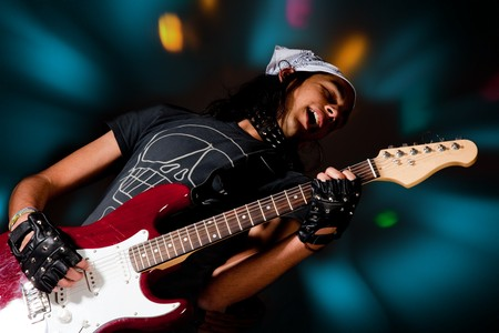 Young handsome rock singer against a dark background with spot lights Stock Photo - 4561820