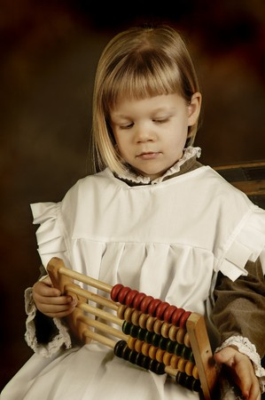 Victorian style photo of a little girl counting with an abacus photo