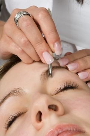 pinzas: Beautician depilating una mujer de cejas con pinzas